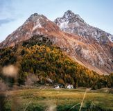 Small houses in Maloja in autumn, Switzerland. Small houses in Maloja village against mountain at sunset in autumn, Maloja Pass, Switzerland Stock Photos