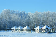 Small houses in snow on frozen lake Royalty Free Stock Images