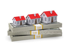 Small houses stand on pack of dollars Stock Images