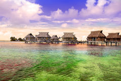 Small houses on water and Seacoast with palm trees Royalty Free Stock Photos