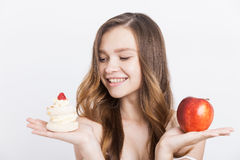 Small human weaknesses. Smiling girl looking at cupcake and deciding to eat it instead of apple. Concept of human weakness stock photos
