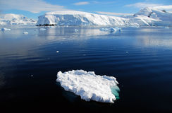 Small iceberg in antarctic landscape. Small ice floe in the sea, with antarctic behind it Royalty Free Stock Photos