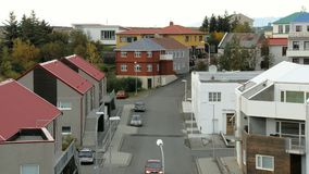 Small icelandic street with houses, parked car in autumn day, one red car is moving. Over road stock video footage