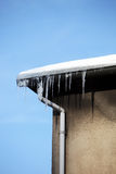 Small icicles hanging from the eaves of a house Stock Photos