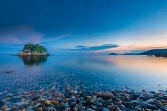 Small idyllic green isle at stoney coast in italy Stock Images