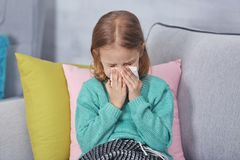 Small ill girl with napkin. At home stock images