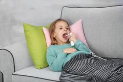Small ill girl with spray on couch. At home Royalty Free Stock Photo