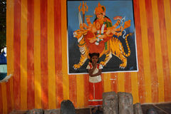 Small indian girl and goddess Durga. Indian girl posing against a wall with the image of hindu goddess Stock Photos