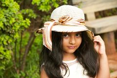Small Indian girl wearing round fancy cap looking at camera, Pune stock photo