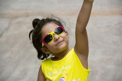 Small Indian girl in a yellow top wearing fancy goggles pointing at something, Pune royalty free stock photography