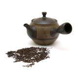 Small individual ceramic teapot and scattered tea Stock Photos