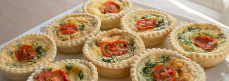 Small Individual Quiche Topped with Tomato and Parsley. Royalty Free Stock Photo