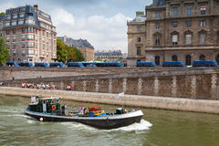 Small industrial boat sails along the quay of river Seine Royalty Free Stock Image