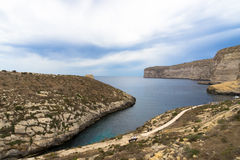 Small inlet next to Xlendi bay. With the Xlendi tower at the horizon Stock Photo