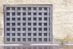 Small iron door  in a wall. Closeup image of a small entrance with iron bars in a wall Royalty Free Stock Image