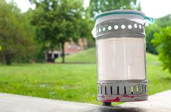 Small iron garbage can in public park with white plastic sign ed Royalty Free Stock Image