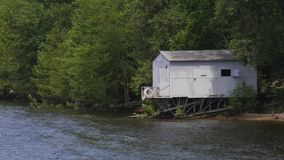 Small iron house on the river bank. The house is surrounded by a green forest stock video footage