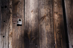 Small iron lock on metal fastener hangs on high wooden gate. Texture, horizontal color photo royalty free stock images