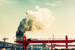 A small iron and steel plant. Huge cranes and chimney smoke of white smoke Royalty Free Stock Photos