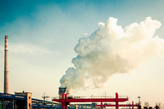 A small iron and steel plant. Huge cranes and chimney smoke of white smoke Stock Images