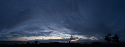 Small island in the Baltic Sea panorama. Single dead tree, sunset and stormy night on the beach. Estonia, Europe. Small island in the Baltic Sea panorama stock photos