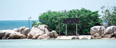 Small island with big rocks and wooden handmade blank sinage in a beach resort stock images