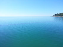 A small island in the blue water of Black Sea. A small island in the blue water and blue sky. Black Sea Coast, seaside Sochi, Russia travel Royalty Free Stock Photo