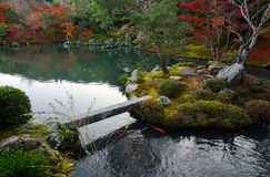 Small island and bridge in a peaceful garden pond in Japan during fall Stock Photography