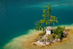 Small island in clean turquoise Wolfgangsee lake in Salzkammergut in Austria Stock Image