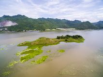 Small island and duckweed in river with mountains background Royalty Free Stock Images