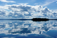 Small Island on Lake. Small island in Karelian lake under blue sky with white clouds stock photography