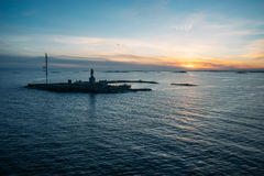 Small island with lighthouse and communication tower. Against scenic sunset stock photo