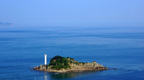 Small island with lighthouse next to Onaruto bridge in Japan Royalty Free Stock Photos