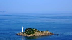 Small island with lighthouse next to Onaruto bridge in Japan Royalty Free Stock Photos