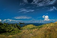 Small island in the ocean, cloudy blue sky, Coromandel Peninsula, New Zealand stock photography