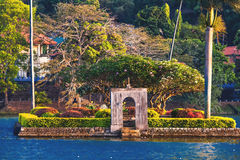 Small island with palm trees in the middle of Kandy lake royalty free stock image
