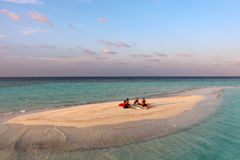 Small island with relaxing people in the Maldives sea Royalty Free Stock Image