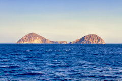 Small island into the sea near Oia Royalty Free Stock Image