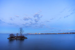 Small island in smooth lake at dusk hiding a nesting swan, safel Royalty Free Stock Image