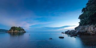 Small island at sunrise with stoney coast Royalty Free Stock Image