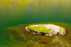 Small island in very clean water of a glacier lake Stock Image