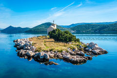 Small island with a very old lighthouse Royalty Free Stock Photo