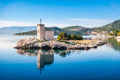 Small island with a very old lighthouse Royalty Free Stock Image
