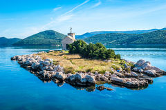 Small island with a very old lighthouse Royalty Free Stock Images