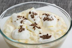 Eggs foam floating on milk flavored with vanilla and lemon peel Stock Photos