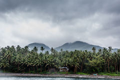 Small isolated hut on the shore of Leyte island with clouds and mountains in background Royalty Free Stock Photos