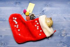 Small items stocking stuffers or fillers little christmas gifts. Christmas sock toned wood background top view. Fill. Sock with gifts or presents. Celebrate stock photo