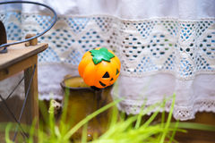 Small Jack o Lantern Decoration in Country Setting. Halloween Still Life - Small Plastic Pumpkin Decoration in Ceramic Vase in front of Table with White Lace stock photo