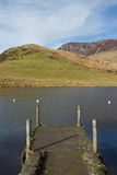 Small jetty. A small jetty landing site made of concrete with wooden posts on a lake in the mountains Stock Images