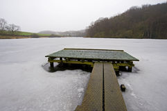Small jetty on a frozen lake. Small wooden jetty for fishing on a frozen lake in the winter Royalty Free Stock Image